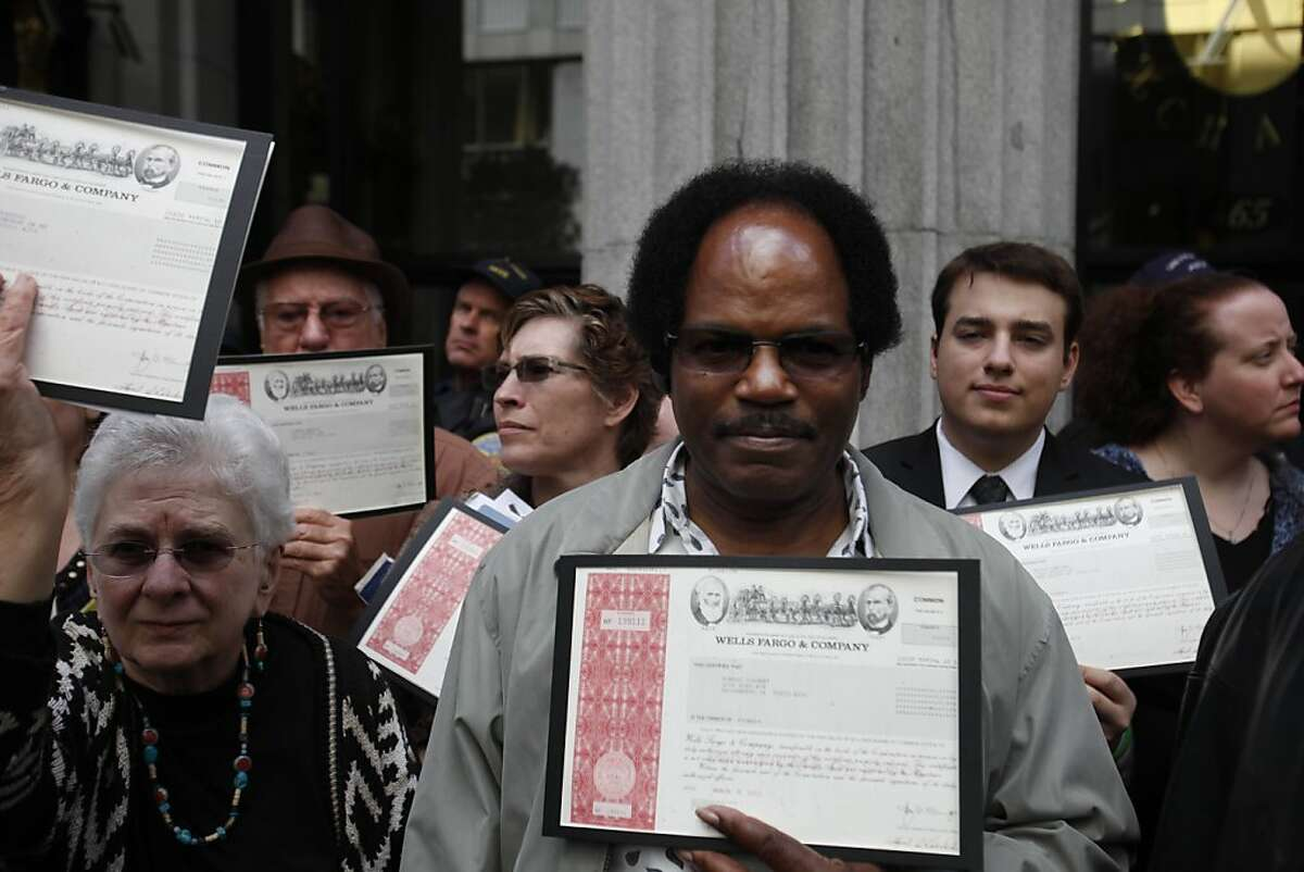 Ronald Colbert of Sacramento holds a certificate with other shareholders as they try to gain access to the Wells Fargo Shareholders' Meeting as they stand outside the Merchants Exchange Building on Tuesday, April 24, 2012 in San Francisco, Calif.