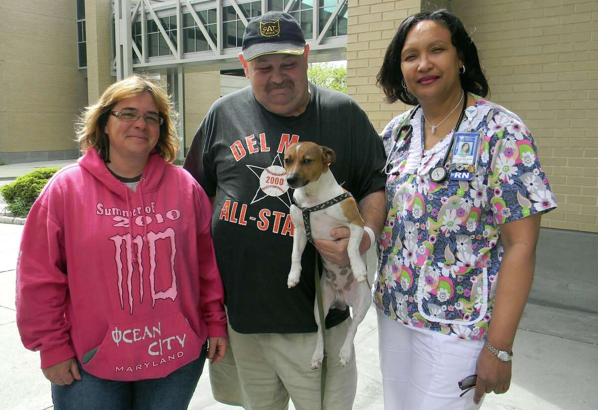 Barnard Plott, center, a truck driver from Citra, FL, holds his Jack Russell terrier, King, in front of Bridgeport Hospital as they pose with Roberta OâÄôDonnell, left, an EMT with American Medical Response, and Lana Mellers, right, Angioplasty Suite Assistant Nurse Manager. OâÄôDonnell took care of King while Plott was recuperating at Bridgeport Hospital following a mild heart attack.