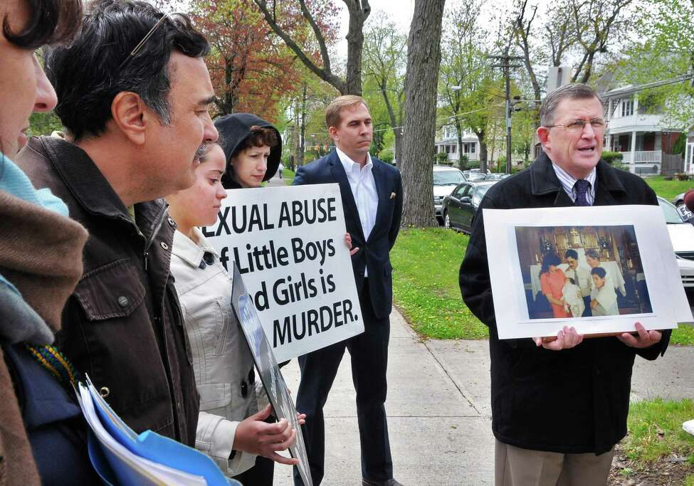 Road to Recovery president Robert Hoatson, at right, holds photos of alleged sexual abuse victims Martin Morales and his brother Ivan Morales Jr. during a news conference outside the Albany Diocesan headquarters in Albany Tuesday April 24, 2012. (John Carl D'Annibale / Times Union)