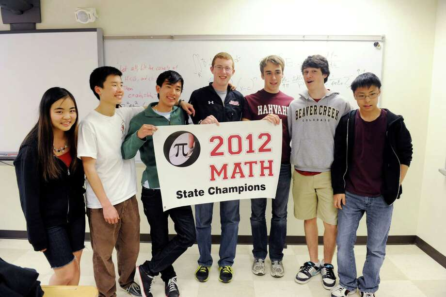 The Greenwich High School math team, from left, Fiona Young, sophomore; Robert Cheng, junior; Ryota Ishizuka, senior; Warren Bein; senior and captain, Connor Harris, senior, captain; Danny Carr, junior; and Thomas Yang, junior, pose with their banner Tuesday, April 24, 2012. For the fourth straight year, the team has won the Connecticut State Association of Mathematics Leagues (CSAML) annual competition. Photo: Helen Neafsey / Greenwich Time