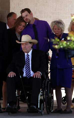 Wison 'Donnie' Golden sits as a family member comforts husband Keith Schuchardt and mother Linda Golden upon the conclusion of the funeral service for Kala Marie Golden-Schuchardt at First Baptist Church on Tuesday, April 24, 2012, in Willis.  Kala Marie Golden-Schuchardt, age 28 of Spring, Texas passed away on Tuesday, April 17, 2012 in the Woodlands. Verna McClain is accused of shooting Kala Golden-Schuchardt to death as she was leaving the Northwoods Pediatric Center, and kidnapping Keegan Schuchardt. Photo: Mayra Beltran, . / © 2012 Houston Chronicle