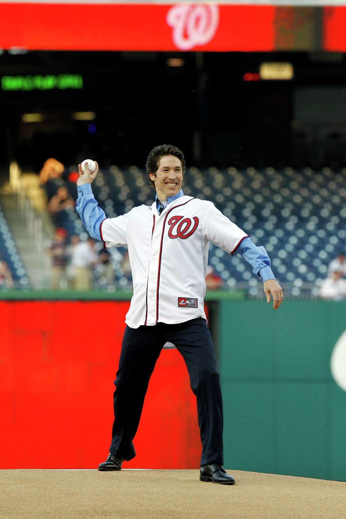 Joel Osteen throws out the ceremonial first pitch prior to a Washington Nationals baseball game against the Houston Astros in Washington, April 16, 2012. (AP Photo/Ann Heisenfelt)