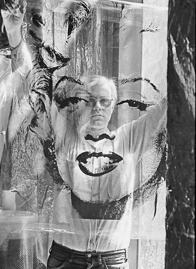 "In this 1964 photo provided by Allen Cooper Enterprises, artist Andy Warhol holds an unrolled acetate of ""Marilyn"" in his New York studio called ""The Factory."" The photo will be featured in an exhibit entitled: ""Before They Were Famous: Behind the Lens of William John Kennedy,"" which runs through April 29, 2012 at the Site/109 gallery in New York. (AP Photo/William John Kennedy via Allen Cooper Enterprises) Photo: William John Kennedy, Associated Press"