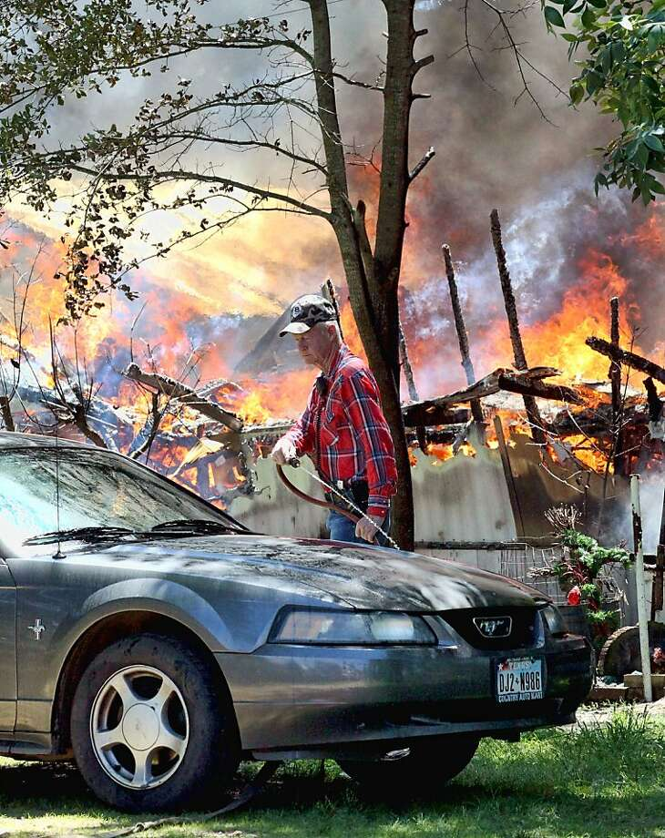 Overheated Mustang:Volunteer firefighter Tom Jordan waters down a car as other firemen try to extinguish a fire that destroyed a home near Powderly, Texas. Jordan said that the house was gone and that he was just trying to save what he could for the homeowner, who escaped the flames with her dog. Photo: Sam Craft, Associated Press