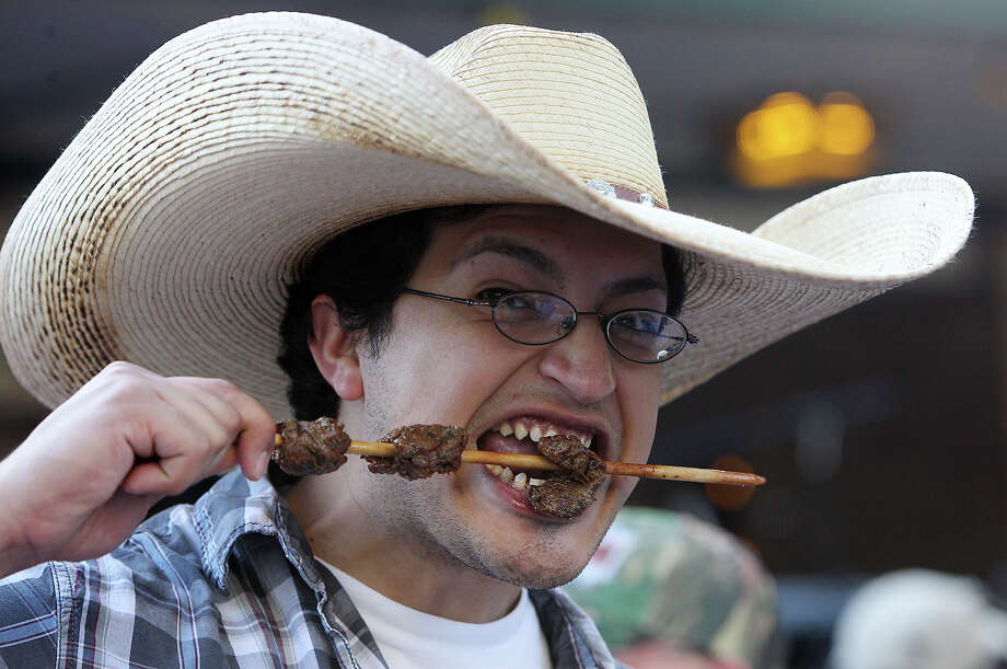 Antonio Guerreo wears a big hat while he takes a big bite from his skewer of anticuchos on the first night of a Night in Old San Antonio on Tuesday, Apr. 24, 2012. Photo: Kin Man Hui, Kin Man Hui/Express-News / ©2012 San Antonio Express-News