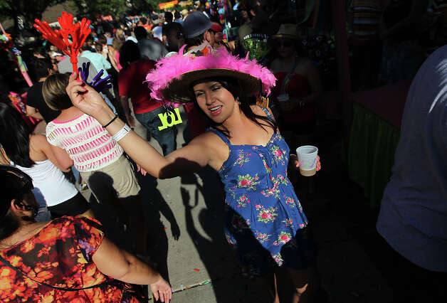 Angie Cruz dons a colorful hat and uses noise makers to attract people to the enchilada booth at the first night of a Night in Old San Antonio on Tuesday, Apr. 24, 2012. Photo: Kin Man Hui, Kin Man Hui/Express-News / ©2012 San Antonio Express-News