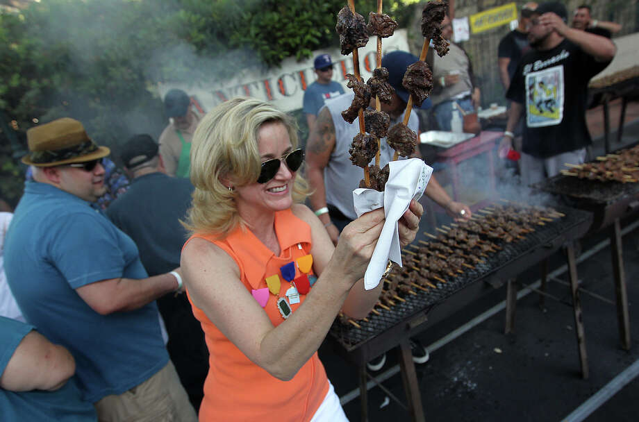 Kathleen O'Shea rushes skewers of anticuchos to awaiting guests at the first night of a Night in Old San Antonio on Tuesday, Apr. 24, 2012. Photo: Kin Man Hui, Kin Man Hui/Express-News / ©2012 San Antonio Express-News