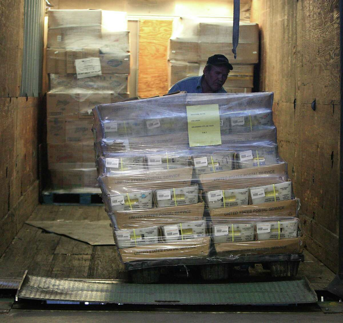 Truck driver Jim Dodson unloads some of the 6,255 pounds of Harris County voter registration cards that are ready to ship Tuesday at the downtown post office.