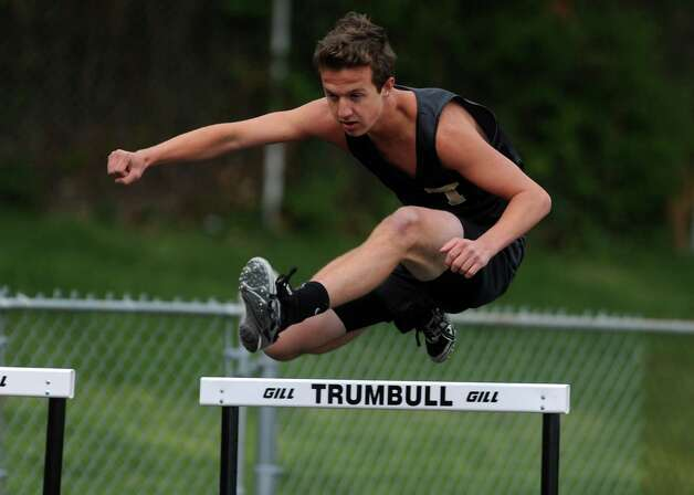 Trumbull's Justin Puzzio competes in the 300 meter hurdles Tuesday, April 24, 2012 during a track meet with Staples and Central at Trumbull High School. Photo: Autumn Driscoll / Connecticut Post