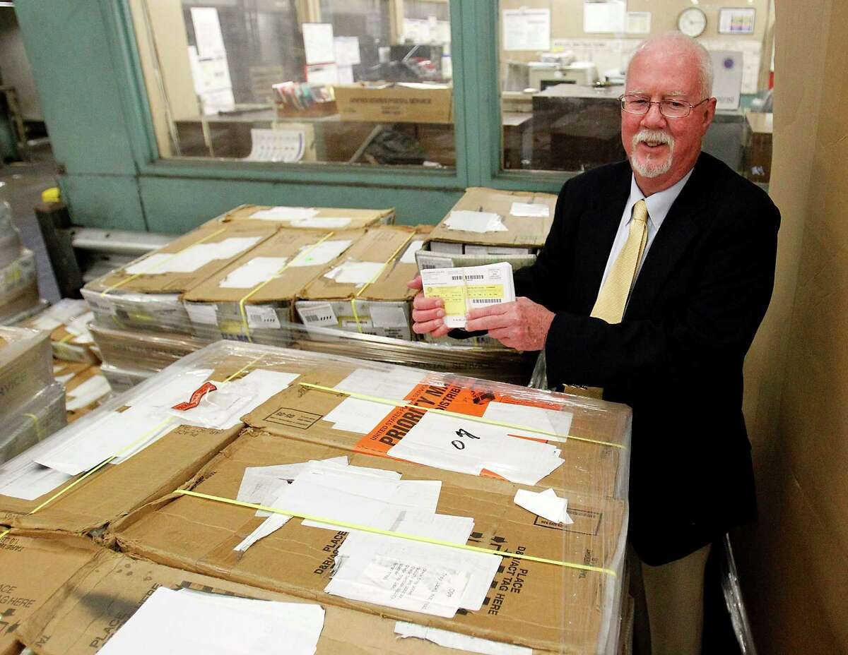 Harris County Tax Assessor-Collector Chief Deputy Jim DeVore, holds up a few of the 1.9 million Harris County voter cards at the main downtown post office, Tuesday, April 24, 2012, in Houston. Harris County received its voter cards, Tuesday, six months late. ( Karen Warren / Houston Chronicle )
