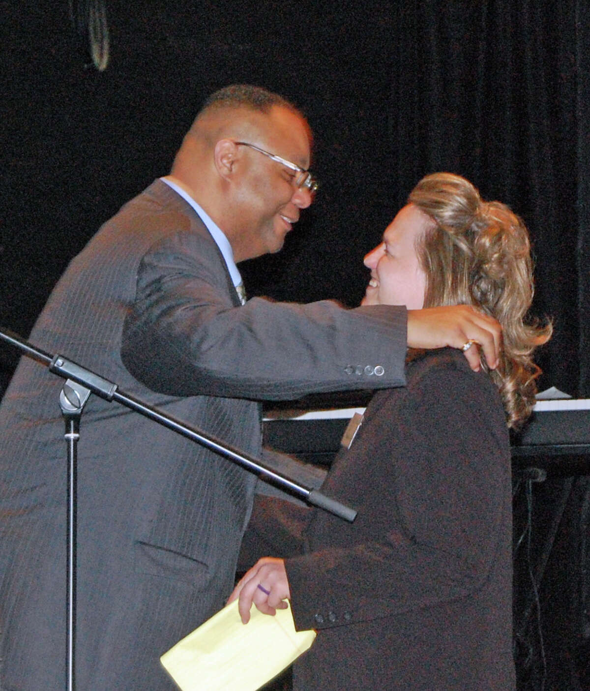 """Alan J Mathis, president and CEO, Liberation Programs, hugs graduate Melissa Oltran during the organization's fourth annual client graduation ceremony, """"A Celebration of Life and New Beginnings."""""""