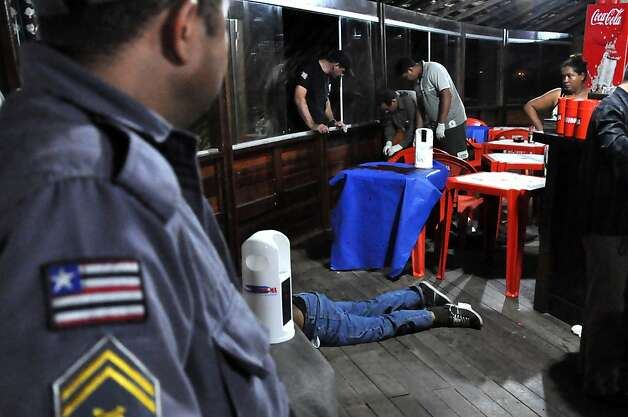 The body of Brazilian journalist Decio Sa, center, lies on the ground after being shot at a restaurant and bar in Sao Luis, Maranhao state, Brazil, Monday, April 23, 2012.  Sa, a political reporter for the O Estado do Maranhao newspaper in northeastern Brazil, is at least the fourth journalist slain this year in the South American nation, one of the deadliest for reporters to work in, according to watchdog groups. Photo: Biaman Prado, Associated Press