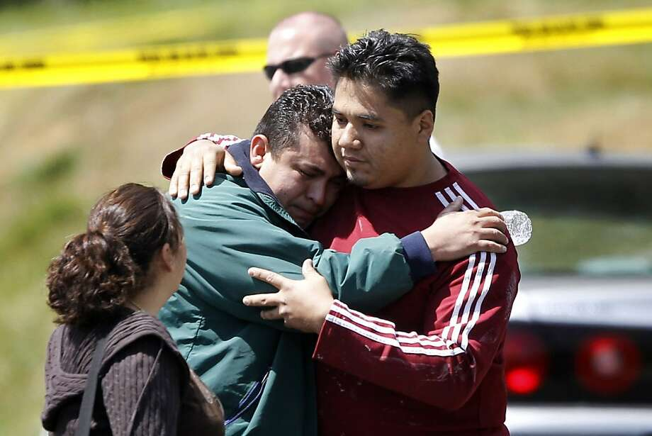 Marvin Chavez Quinteros, center, who discovered the bodies in his father's home, is comforted in Oxon Hill, Md., Tuesday, April 24, 2012. Five people are dead in a Maryland suburb of Washington of suspected carbon monoxide poisoning. (AP Photo/Charles Dharapak) Photo: Charles Dharapak, Associated Press