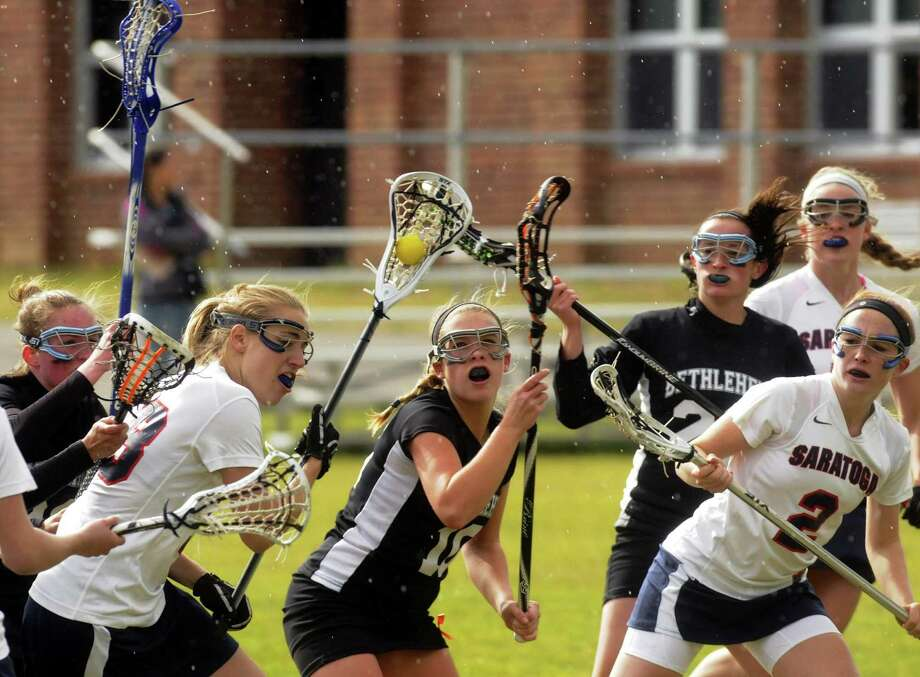 Saratoga Springs Emily Lange, left, battles through defenders during their high school girls lacrosse game against Bethlehem in Saratoga Springs N.Y. Tuesday April 24, 2012. (Michael P. Farrell/Times Union) Photo: Michael P. Farrell