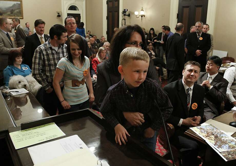 Trace Conard, 5, of Corning, is held up to the microphone by his mother, Jodie, as he urged lawmakers to vote against a bill that would ban the use of dogs to hunt bears and bobcats, during a hearing of the Senate Natural Resources and Water Committee at the Capitol in Sacramento, Calif., Tuesday, April 24, 2012. After  more than two hours of testimony the bill, SB1221 by Sen. Ted Lieu, D-Torrence, was approved by a 5-3 vote. (AP Photo/Rich Pedroncelli) Photo: Rich Pedroncelli, Associated Press