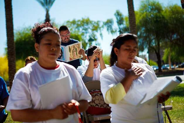 PHOENIX, AZ - APRIL 24:  A protester opposed to Arizona's Immigration Law SB 1070 bows her head in prayer during a vigil held at the Arizona state Capitol April 24, 2012 in Phoenix, Arizona. The United Farm Workers (UFW) has planned a day of protest and vigils at the Arizona state Capitol April 24, the day before the U.S. Supreme Court hears arguments over Arizona's 2010 immigration enforcement law. (Photo by Jonathan Gibby/Getty Images)  *** BESTPIX *** Photo: Jonathan Gibby, Getty Images