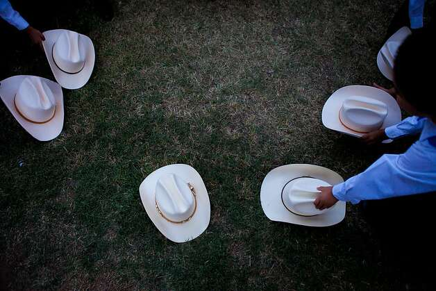 PHOENIX, AZ - APRIL 24:  Children pick up their hats during a vigil for those opposed to Arizona's Immigration Law SB 1070 at the Arizona state Capitol April 24, 2012 in Phoenix, Arizona. The United Farm Workers (UFW) has planned a day of protest and vigils at the Arizona state Capitol April 24, the day before the U.S. Supreme Court hears arguments over Arizona's 2010 immigration enforcement law. (Photo by Jonathan Gibby/Getty Images) Photo: Jonathan Gibby, Getty Images