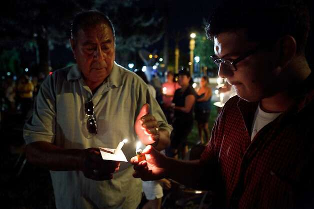 PHOENIX, AZ - APRIL 24:  A volunteer helps light candles during a vigil held for those opposed to Arizona's Immigration Law SB 1070 at the Arizona state Capitol April 24, 2012 in Phoenix, Arizona. The United Farm Workers (UFW) has planned a day of protest and vigils at the Arizona state Capitol April 24, the day before the U.S. Supreme Court hears arguments over Arizona's 2010 immigration enforcement law. (Photo by Jonathan Gibby/Getty Images) Photo: Jonathan Gibby, Getty Images