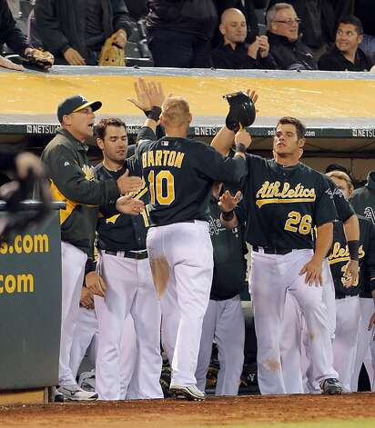 The A's celebrate with Daric Barton after Barton scored the winning run on a Kurt Suzuki double in the bottom of the eighth inning. The Oakland Athletics played the Chicago White Sox at the O.co Coliseum in Oakland, Calif., on Tuesday, April 24, 2012. The A's defeated the Sox 2-0. Photo: Carlos Avila Gonzalez, The Chronicle