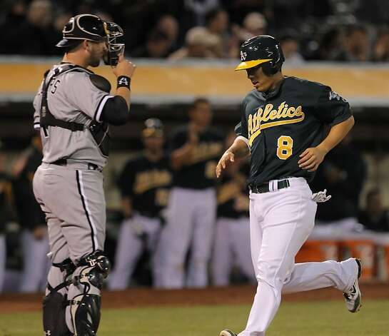 Kurt Suzuki scores in the eighth off a single by Eric Sogard. Suzuki had the game-winning RBI in that inning. The Oakland Athletics played the Chicago White Sox at the O.co Coliseum in Oakland, Calif., on Tuesday, April 24, 2012. The A's defeated the Sox 2-0. Photo: Carlos Avila Gonzalez, The Chronicle