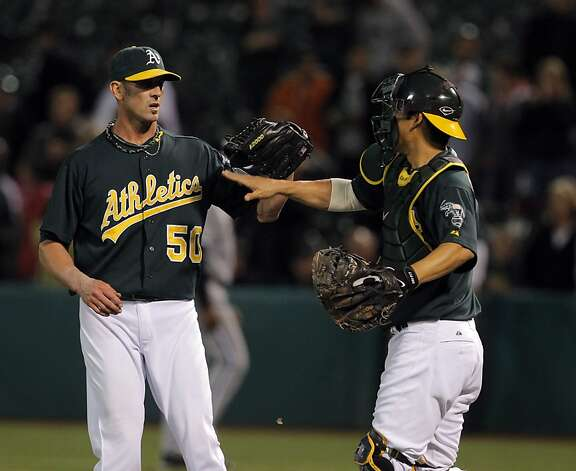Grant Balfour and Kurt Suzuki high five after the game. The Oakland Athletics played the Chicago White Sox at the O.co Coliseum in Oakland, Calif., on Tuesday, April 24, 2012. The A's defeated the Sox 2-0. Photo: Carlos Avila Gonzalez, The Chronicle