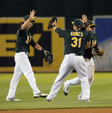 A's outfielders, Josh Reddick, left, Johnny Gomes, center, and Yoenis Cespedes celebrate after the A's victory. The Oakland Athletics played the Chicago White Sox at the O.co Coliseum in Oakland, Calif., on Tuesday, April 24, 2012. The A's defeated the Sox 2-0. Photo: Carlos Avila Gonzalez, The Chronicle