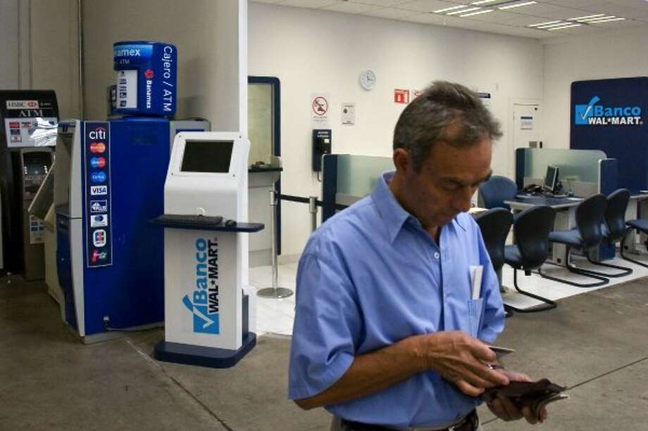A customer puts his credit card away after withdrawing money at a Wal-Mart bank inside a Sam's Club store in Curenavaca, Mexico, on Thursday, Jan. 24, 2008. Wal-Mart de Mexico SAB's bank unit, which started operations in November 2007, will introduce checking accounts, credit cards, payroll accounts and loans for small companies in 2008, and currently offers free savings accounts and personal credit for in-store purchases up to 50,000 pesos ($4,590). Photographer: Trevor Snapp/Bloomberg News (BLOOMBERG NEWS)