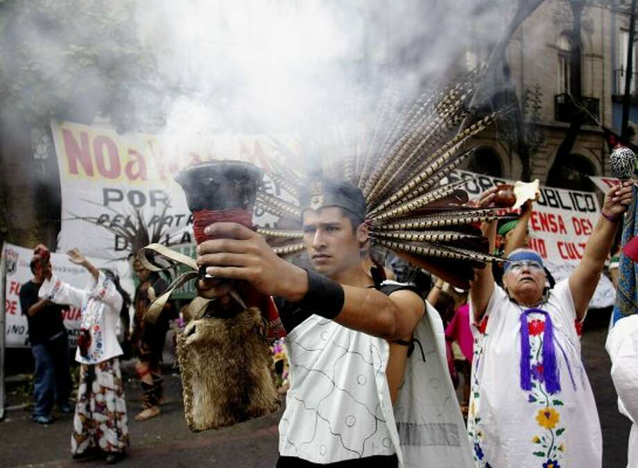 protesters, some wearing a traditional Aztec dress burns ceremonial incense in front of the offices of the national institute of anthropology and history in Mexico City, during a protest against the construction of a Wal-Mart store near Mexico's Teotihuacan archeological ruins, October 31, 2004. The construction of the Wal-Mart-owned Aurrera hypermarket near the pre-hispanic ruins at Teotihuacan have attracted protest from groups who oppose such a large commercial center so near to such an archaeological treasure.  REUTERS/Henry Romero.  HOUCHRON CAPTION  (11/01/2004) SECNEWS:  PROTESTERS, some wearing traditional Aztec dress, burn ceremonial incense Sunday in front of the offices of the National Institute of Anthropology and History in Mexico City in a demonstration against the construction of a Wal-Mart store near Mexico's Teotihuacan archaeological ruins. (REUTERS)