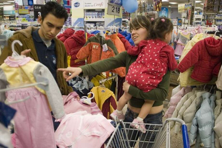 "Alejandro Garcia Aguilar, 20, his wife Claudia de Leon, 18 and their daughter Gaby Garcia de Leon, 1 1/2 years old, shop for children's clothes in Walmart in Mexico City on December 14, 2006.  Alejandro Garcia works at Walmart and might open an account when they begin their banking services, depending on their interest rates.  ""I hope that Walmart will have better interest rates than the other banks"", said Alejandro Garcia Aguilar.  (Photo By Sarah Meghan Lee) (Sarah Meghan Lee)"