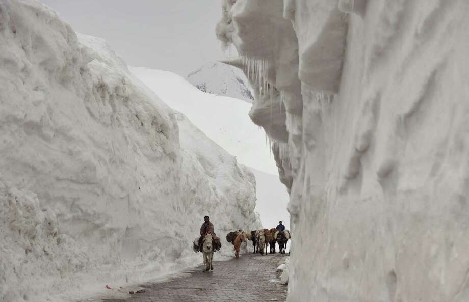 Kashmiri porters on horseback travel past walls of snow along the newly-reopened Srinagar-Leh highway in Zojila, about 108 km (67 miles) east of Srinagar, on April 25, 2012. The 443 km (275 mile) long highway was opened for the season by Indian Army authorities after remaining snow at Zojila Pass, some 3,530 metres (11,581 feet) above sea level, had been cleared. The pass connects Kashmir with the Buddhist-dominated Ladakh region, a famous tourist destination among foreign tourists for its monasteries, landscapes and mountains. AFP PHOTO/Tauseef MUSTAFA Photo: TAUSEEF MUSTAFA, AFP/Getty Images / AFP