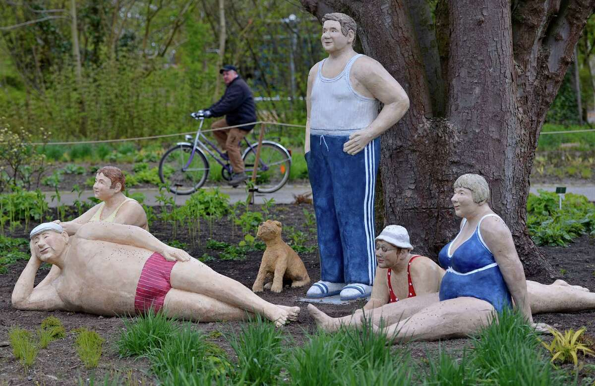 A man on a bicycle passes by life-size figures made of concrete by artist Cristel Lechner at the Maximilian park in Hamm, western Germany, Wednesday. The German artist installed 80 figures open air all over the park for her exhibition
