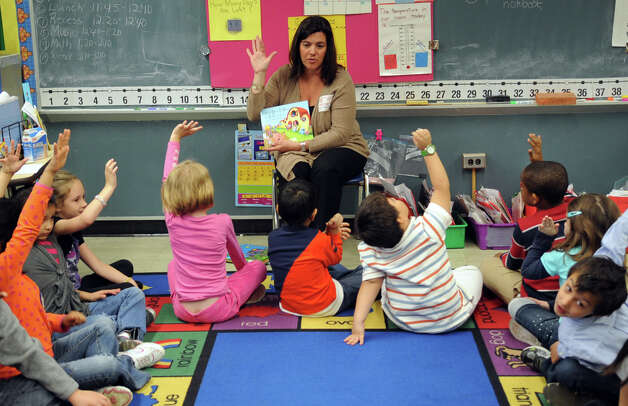 "Tracie Wilson, Senior Vice President of Programming and Development for Stamford Media Center, reads to first grade students in Sue Rubeck's class at Toquam Magnet School in Stamford on Wedneday, April 25, 2012, as part of the Volunteer Center of Southwestern Fairfield County's annual ""Business to Books"" read-a-thon. Photo: Lindsay Niegelberg / Stamford Advocate"