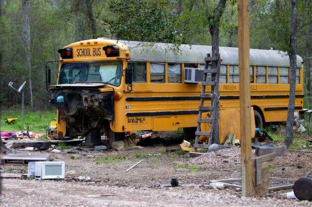 An old school bus is said to be where two young children were found living on their own Wednesday, March 7, 2012, in Spendora. An 11-year-old girl is said to be living in the bus with her five-year-old brother. Both of the children's parents were, at the time, in prison, officials said. Photo: Brett Coomer, Houston Chronicle /  2012 Houston Chronicle