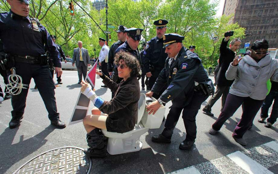 Police prepare to arrest a protester on a toilet during a demonstration around the Wall Street financial district on Wednesday, April 25, 2012 in New York. Members of  the AIDS Coalition to Unleash Power and other groups have chained themselves together and blocked traffic in the Wall Street area. (AP Photo/Bebeto Matthews) Photo: Bebeto Matthews, Associated Press / AP