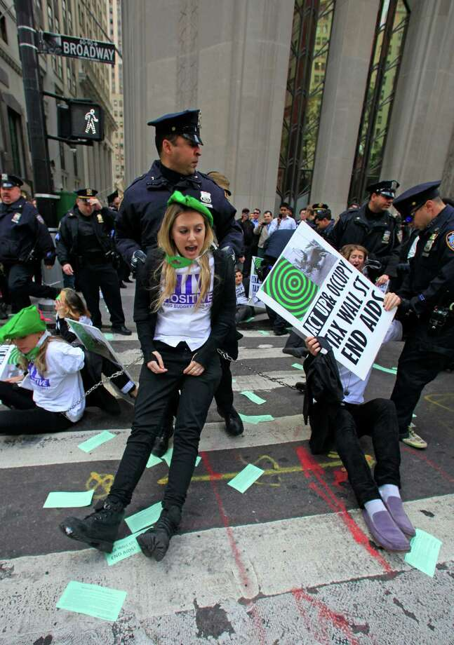 Police arrest members of a combined group of ACT UP and Occupy Wall Street activists who chained themselves and block traffic at Wall Street and Broadway, near the New York Stock Exchange, on Wednesday, April 25, 2012.  Police used chain cutters and wrestled protesters to the pavement in the middle of Broadway. (AP Photo/Bebeto Matthews) Photo: Bebeto Matthews, Associated Press / AP