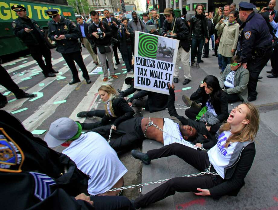 Police prepare to arrest members of a combined group of ACT UP and Occupy Wall Street activists who chained themselves and block traffic at Wall Street and Broadway, near the New York Stock Exchange, on Wednesday, April 25, 2012.  Police used chain cutters and wrestled protesters to the pavement in the middle of Broadway. (AP Photo/Bebeto Matthews) Photo: Bebeto Matthews, Associated Press / AP