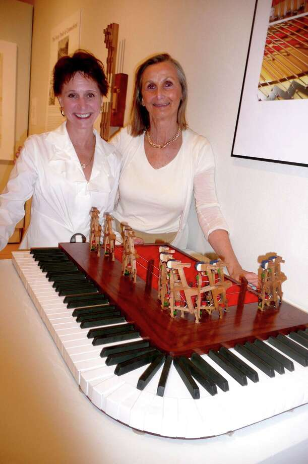 "Greenwich artists Shauna Holiman, left, and Penny Putnam have collaborated to create new art from the innards of pianos - the ivories, hammers and pedals. Here, they stand with one of their pieces on display in an exhibit of their work,""Piano Pieces"" at the Flinn Gallery through May 3. Photo: Anne W. Semmes"
