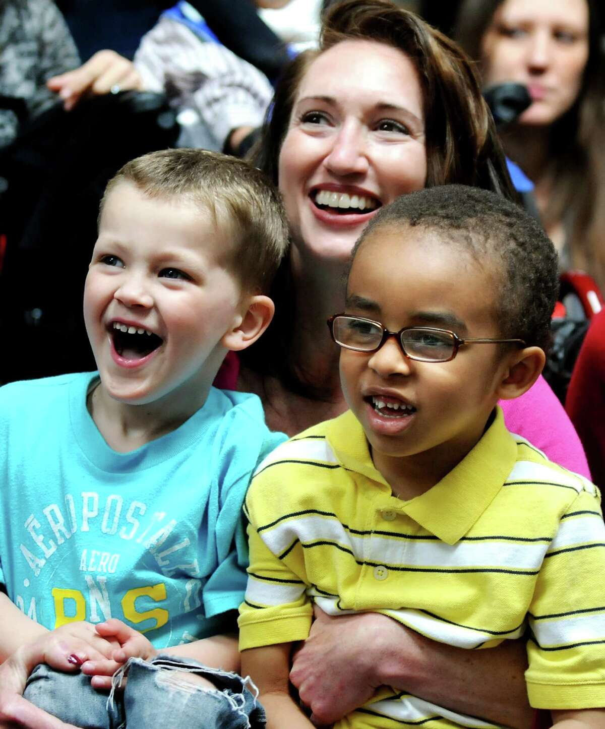 Robert Smart, 3, left, and Evin Witt, 4, right, laugh with Bonnie White, a speech pathologist, as they watch Ringling Bros. and Barnum & Bailey clowns perform on Wednesday, April 25, 2012, at the Center for Disability Services in Albany, N.Y. (Cindy Schultz / Times Union)