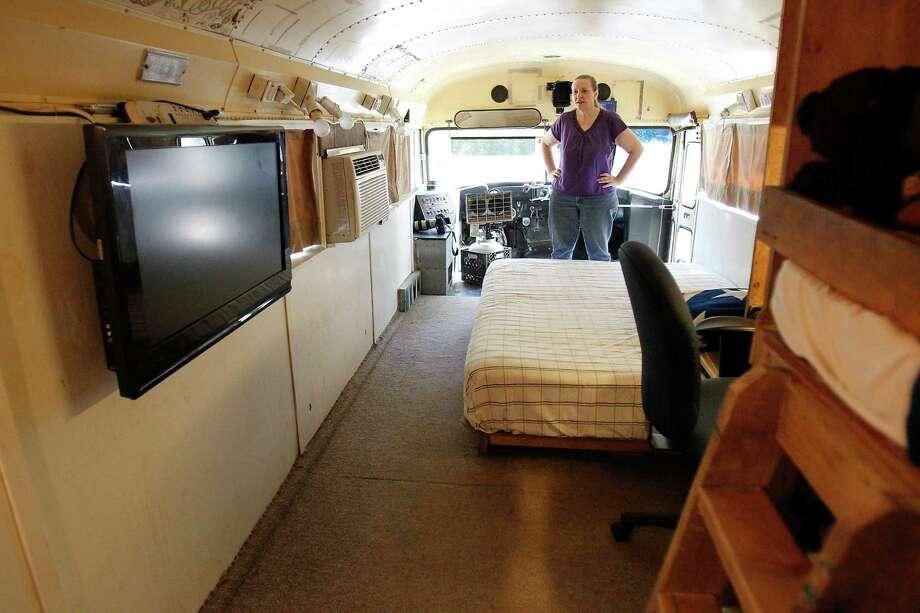 Sherrie Shorten stands inside of the bus she calls home. Photo: Karen Warren, Houston Chronicle / © 2012  Houston Chronicle