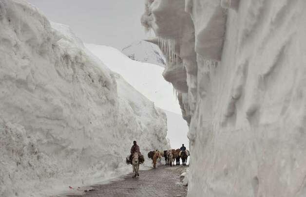 Kashmiri porters on horseback travel past walls of snow along the newly reopened Srinagar-Leh highway in Zojila, about 67 miles east of Srinagar, on Wednesday. The 275-mile-long highway was opened for the season by Indian Army authorities after remaining snow at Zojila Pass, some 11,581 feet above sea level, had been cleared. The pass connects Kashmir with the Buddhist-dominated Ladakh region, a famous tourist destination among foreign tourists for its monasteries, landscapes and mountains. AFP PHOTO/Tauseef MUSTAFA Photo: TAUSEEF MUSTAFA, AFP/Getty Images / 2012 AFP