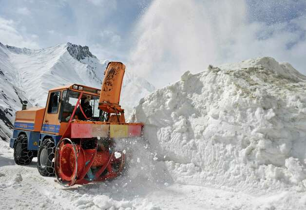 A snow clearing vehicle cuts through snowdrifts at the Srinagar-Leh highway in Zojila, about 67 miles east of Srinagar, on Wednesday. The 275-mile highway was opened for the season by Indian Army authorities after remaining snow at Zojila Pass, some 11,581 feet above sea level, had been cleared. The pass connects Kashmir with the Buddhist-dominated Ladakh region, a famous tourist destination among foreign tourists for its monasteries, landscapes and mountains. AFP PHOTO/Tauseef MUSTAFA Photo: TAUSEEF MUSTAFA, AFP/Getty Images / 2012 AFP