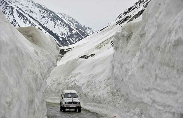 A vehicle plies the Srinagar-Leh highway in Zojila, about 67 miles east of Srinagar, on Wednesday. The 275-mile highway was opened for the season by Indian Army authorities after remaining snow at Zojila Pass, some 11,581 feet above sea level, had been cleared. The pass connects Kashmir with the Buddhist-dominated Ladakh region, a famous tourist destination among foreign tourists for its monasteries, landscapes and mountains. AFP PHOTO/Tauseef MUSTAFA Photo: TAUSEEF MUSTAFA, AFP/Getty Images / 2012 AFP