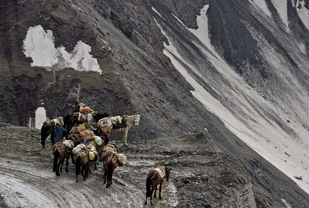 Kashmiri porters with their horses look on from the newly reopened Srinagar-Leh highway in Zojila Pass, about 67 miles east of Srinagar, on Wednesday. The 275-milehighway was opened for the season by Indian Army authorities after remaining snow at Zojila Pass, some 11,581 feet above sea level, had been cleared. The pass connects Kashmir with the Buddhist-dominated Ladakh region, a famous tourist destination among foreign tourists for its monasteries, landscapes and mountains. AFP PHOTO/Tauseef MUSTAFA Photo: TAUSEEF MUSTAFA, AFP/Getty Images / 2012 AFP