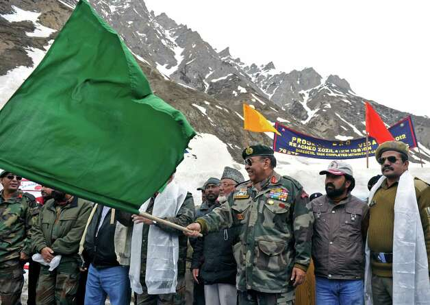 Chief commander of India's Srinagar-based 15 Army Corps Signals Syed Ata Hasnain flags off vehicles departing on the newly-reopened Srinagar-Leh highway in Zojila, about 67 miles east of Srinagar, on Wednesday. The 275-mile highway was opened for the season by Indian Army authorities after remaining snow at Zojila Pass, some 11,581 feet above sea level, had been cleared. The pass connects Kashmir with the Buddhist-dominated Ladakh region, a famous tourist destination among foreign tourists for its monasteries, landscapes and mountains. AFP PHOTO/Tauseef MUSTAFA Photo: TAUSEEF MUSTAFA, AFP/Getty Images / 2012 AFP