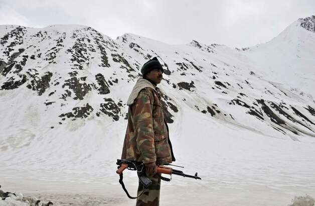 An Indian soldier keeps watch along the Srinagar-Leh highway in Zojila, about 67 miles east of Srinagar, on Wednesday. The 275-mile highway was opened for the season by Indian Army authorities after remaining snow at Zojila Pass, some 11,581 feet above sea level, had been cleared. The pass connects Kashmir with the Buddhist-dominated Ladakh region, a famous tourist destination among foreign tourists for its monasteries, landscapes and mountains. AFP PHOTO/Tauseef MUSTAFA Photo: TAUSEEF MUSTAFA, AFP/Getty Images / 2012 AFP