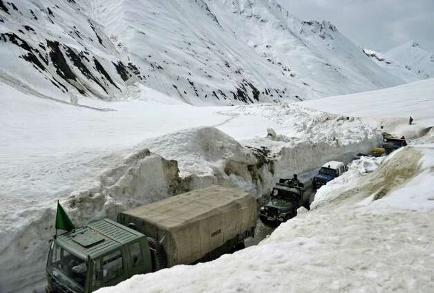 Military vehicles ply the Srinagar-Leh highway in Zojila, about 67 miles east of Srinagar, on Wednesday. The 275-milehighway was opened for the season by Indian Army authorities after remaining snow at Zojila Pass, some 11,581 feet above sea level, had been cleared. The pass connects Kashmir with the Buddhist-dominated Ladakh region, a famous tourist destination among foreign tourists for its monasteries, landscapes and mountains. AFP PHOTO/Tauseef MUSTAFA Photo: TAUSEEF MUSTAFA, AFP/Getty Images / 2012 AFP