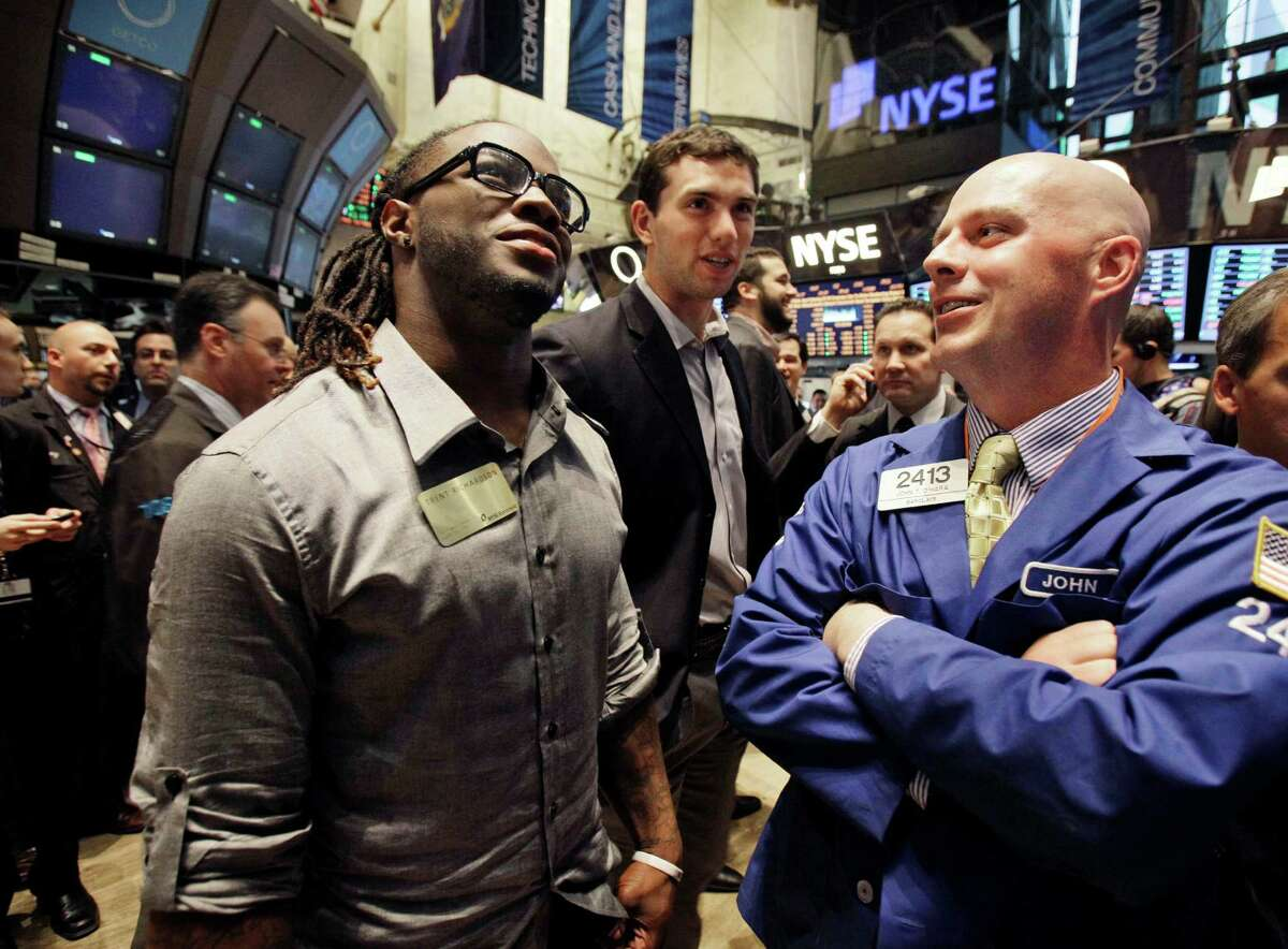NFL football draft prospects Trent Richardson, of Alabama, left, and Andrew Luck, of Stanford, center, talk with specialist John O'Hara during their visit to the trading floor of the New York Stock Exchange, Wednesday, April 25, 2012. The college stars are preparing for the NFL draft Thursday night at Radio City Music Hall.