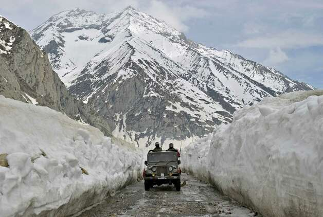 An Indian Army jeep plies the Srinagar-Leh highway in Zojila, about 67 miles east of Srinagar, on Wednesday. The 275-mile highway was opened for the season by Indian Army authorities after remaining snow at Zojila Pass, some 11,581 feet above sea level, had been cleared. The pass connects Kashmir with the Buddhist-dominated Ladakh region, a famous tourist destination among foreign tourists for its monasteries, landscapes and mountains. AFP PHOTO/Tauseef MUSTAFA Photo: TAUSEEF MUSTAFA, AFP/Getty Images / 2012 AFP