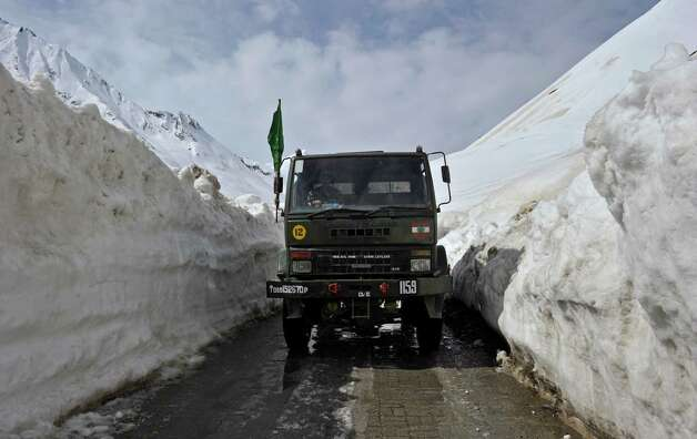 An Indian Army truck plies the Srinagar-Leh highway in Zojila, about 67 miles east of Srinagar, on Wednesday. The 275-mile highway was opened for the season by Indian Army authorities after remaining snow at Zojila Pass, some 11,581 feet above sea level, had been cleared. The pass connects Kashmir with the Buddhist-dominated Ladakh region, a famous tourist destination among foreign tourists for its monasteries, landscapes and mountains. AFP PHOTO/Tauseef MUSTAFA Photo: TAUSEEF MUSTAFA, AFP/Getty Images / 2012 AFP
