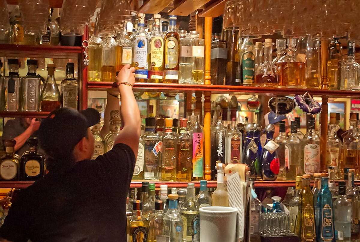 Bartender Greedy Balam puts a Tequila bottle on the shelf at Tommy's Mexican Restaurant in San Francisco, Calif., on Monday April 23rd, 2012.